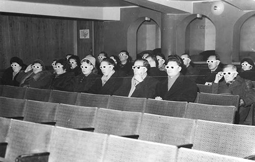 """3:s ulottuvaisuus esiin (1953). Ohjaus: Alvar Hamberg. """"Kuva otettu elokuvateatteri Aritassa, missä kutsuvieraat katsovat lyhytkuvaa punavihreitten sellofaanilasien läpi."""" Kuva: KAVI. © YLE."""